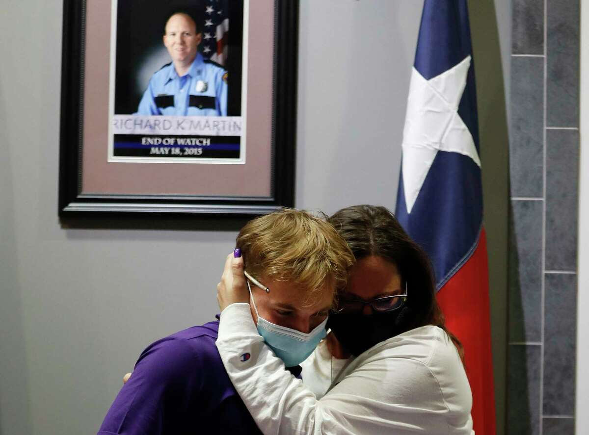 With a picture of his father, slain Houston police officer Richard Martin, behind him Wednesday, Tyler Martin hugs his mother, Kim, after signing his letter of intent to play baseball at Mary Hardin-Baylor. Many officers were at the Westside Command Station to wish Tyler well, as was Lieutenant Governor Dan Patrick.