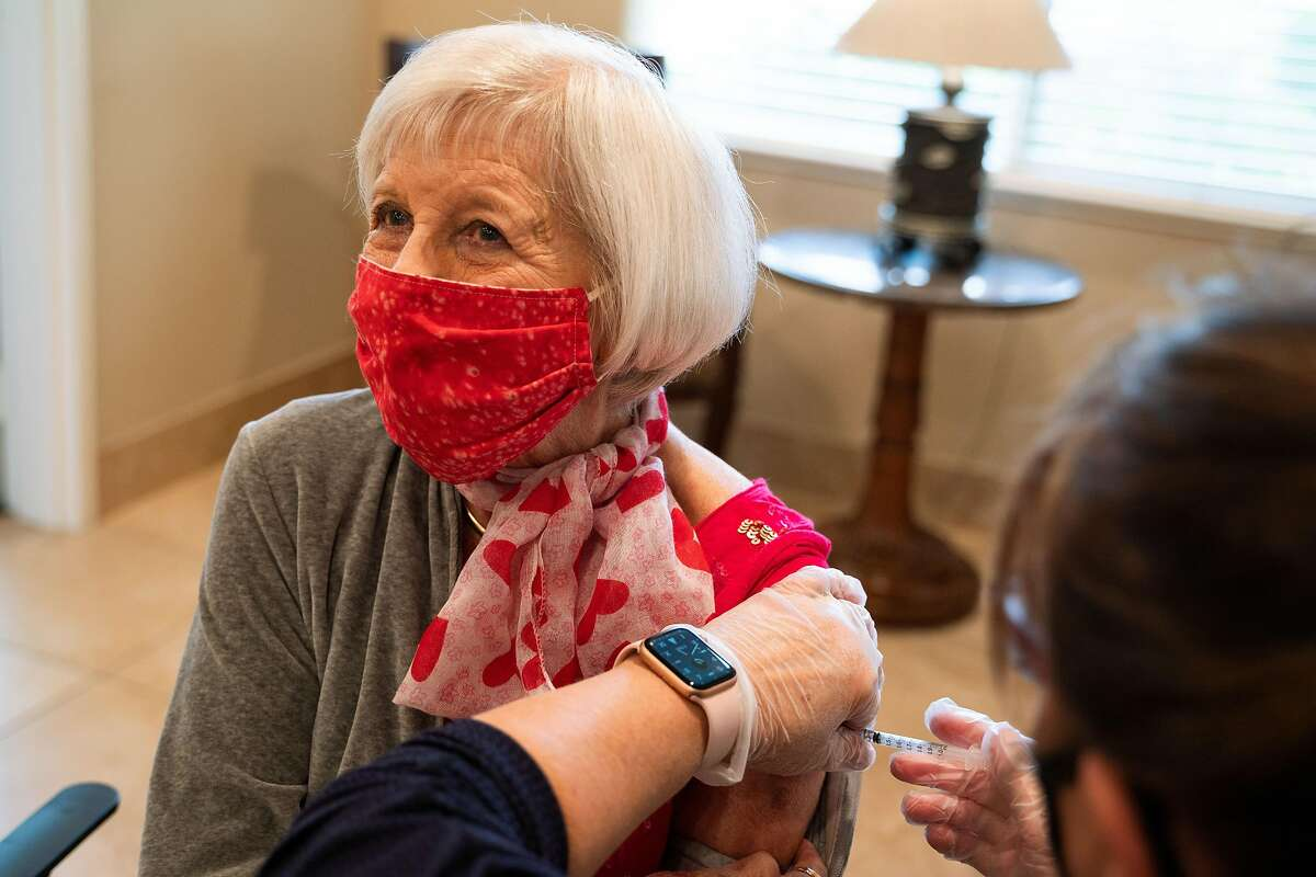 Bev Cullen, 80, receives her second dose of the COVID-19 vaccine from nurse Debbie Outcalt at Oakmont of Montecito assisted living facility.