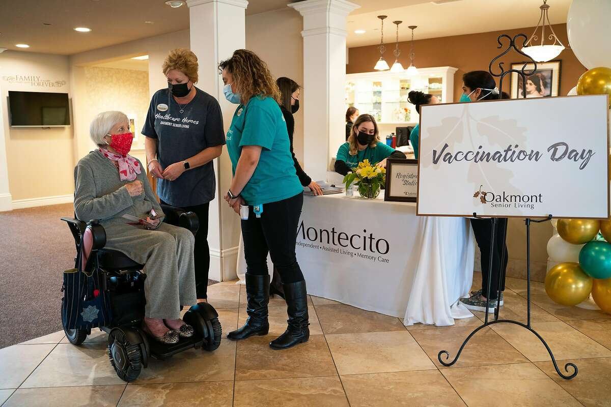 Bev Cullen, 80, talks with staff members Michaela Olson (center) and Melinda Alvarez while waiting to receive her second dose of the vaccine at Oakmont of Montecito assisted living facility in Concord.