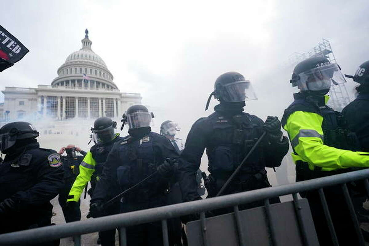 Police stand guard after holding off rioters who tried to break through a police barrier at the Capitol in Washington, D.C., in January. As federal officials grapple with how to confront the national security threat from domestic extremists after the deadly siege of the Capitol, civil rights groups and communities of color are watching warily for any moves to expand law enforcement power or authority.