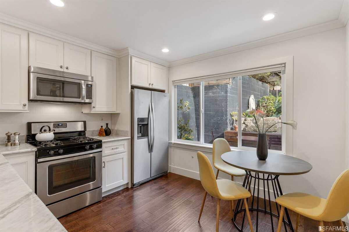 The efficient kitchen is remodeled with stainless steel appliances, marble countertops and a small eat-in area.