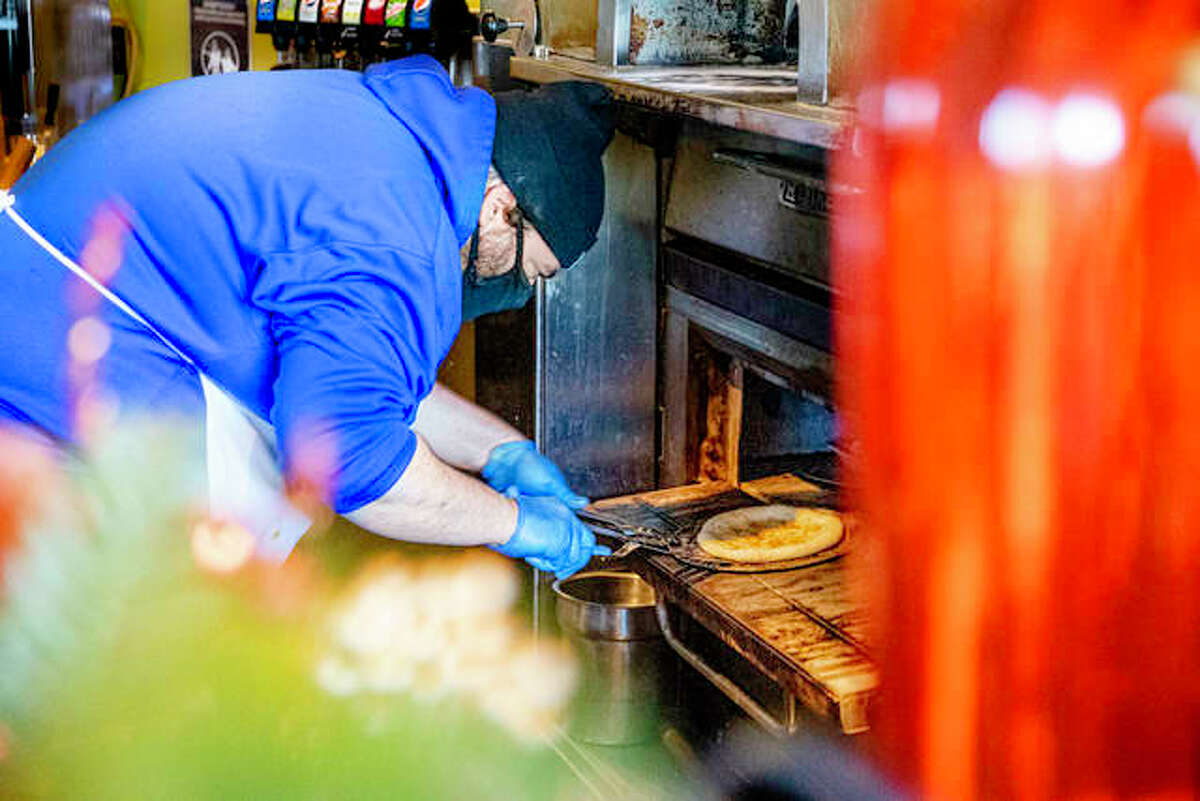 Bella Milano sous-chef Brandon Moses pulls pita dough out of the oven on late last year.
