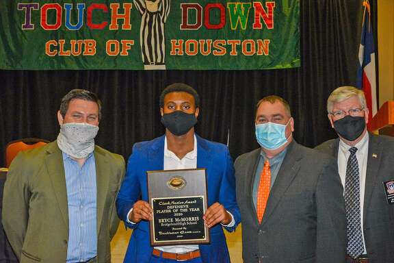Bridgeland senior defensive back Bryce McMorris holds a plaque next to Bridgeland Head Coach David Raffield (second from the right) and representatives of the Touchdown Club of Houston after McMorris was named Defensive Player of the Year on Jan. 20, 2021.