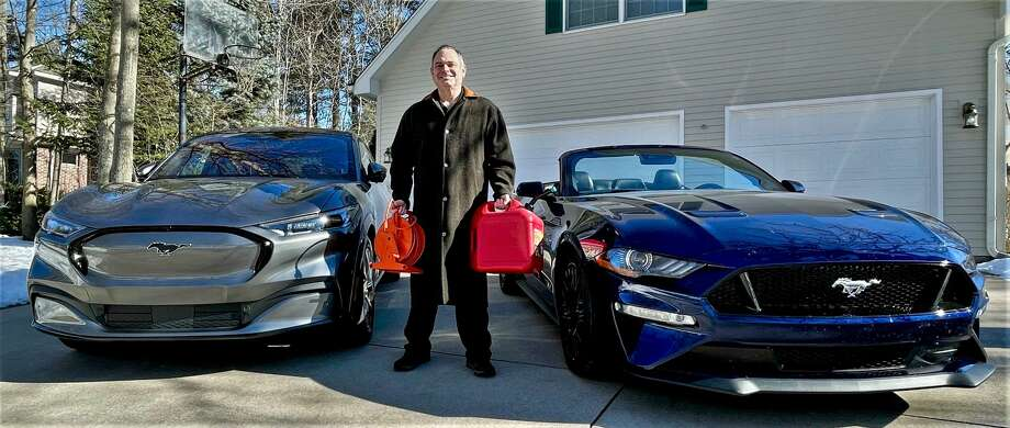 Midland resident Chris Light poses for a photo with his new Mustang Mach-E First Edition, left, and his 2019 Mustang GT convertible 5.0L V8, right, with an electrical cord in one hand and a gas can in the other, signaling the different fuel sources needed for the two Mustangs. Light picked up his Mach-E from Midland Ford this week. (Photo provided/Chris Light) Photo: (Photo Provided/Chris Light)