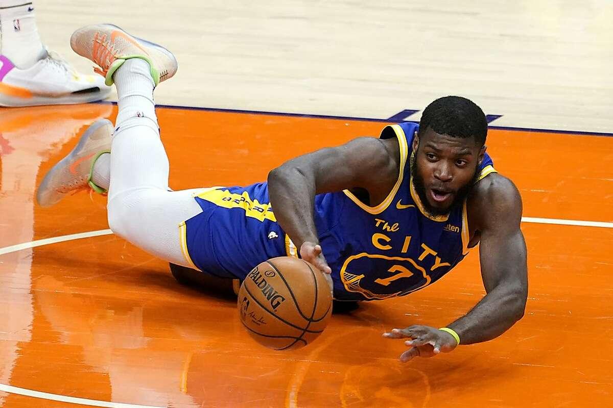 Golden State Warriors forward Eric Paschall passes the ball as he falls during the first half of the team's NBA basketball game against the Phoenix Suns, Thursday, Jan. 28, 2021, in Phoenix. (AP Photo/Matt York)