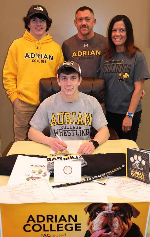 Midland High senior Connor Schelb poses after signing his National Letter of Intent to wrestle at Adrian College. He is flanked by his younger brother Cole, also an MHS wrestler, and his parents Chris and Nicole. Photo: Photo Provided