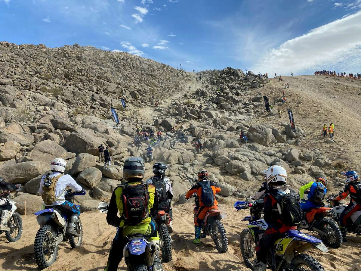 Motorcyclists race up a rocky mountain.