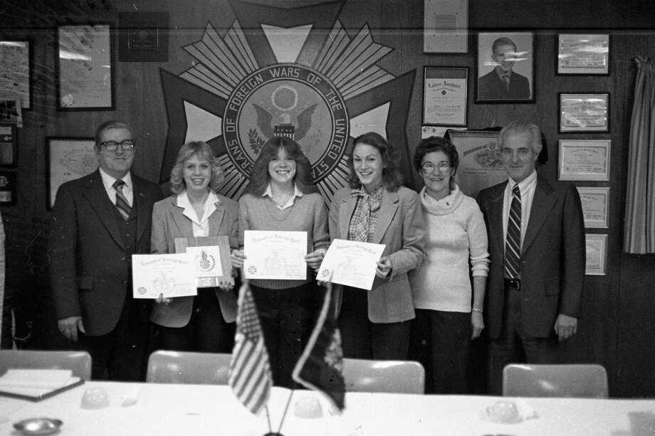 """Winners of the Veterans of Foreign Wars'annual """"Voice of Democracy"""" contest were honored over the weekend. From left, VFW Post Commander Russ Koeman stands with winners Wendy Seng, Julie Hull and Joyce Wilson along with Marie Konicki, VFW Ladies Auxiliary president and Chuck Herbert, Voice of Democracy contest chairman. The photo was published on this day in 1981. (Manistee County Historical Museum photo)"""