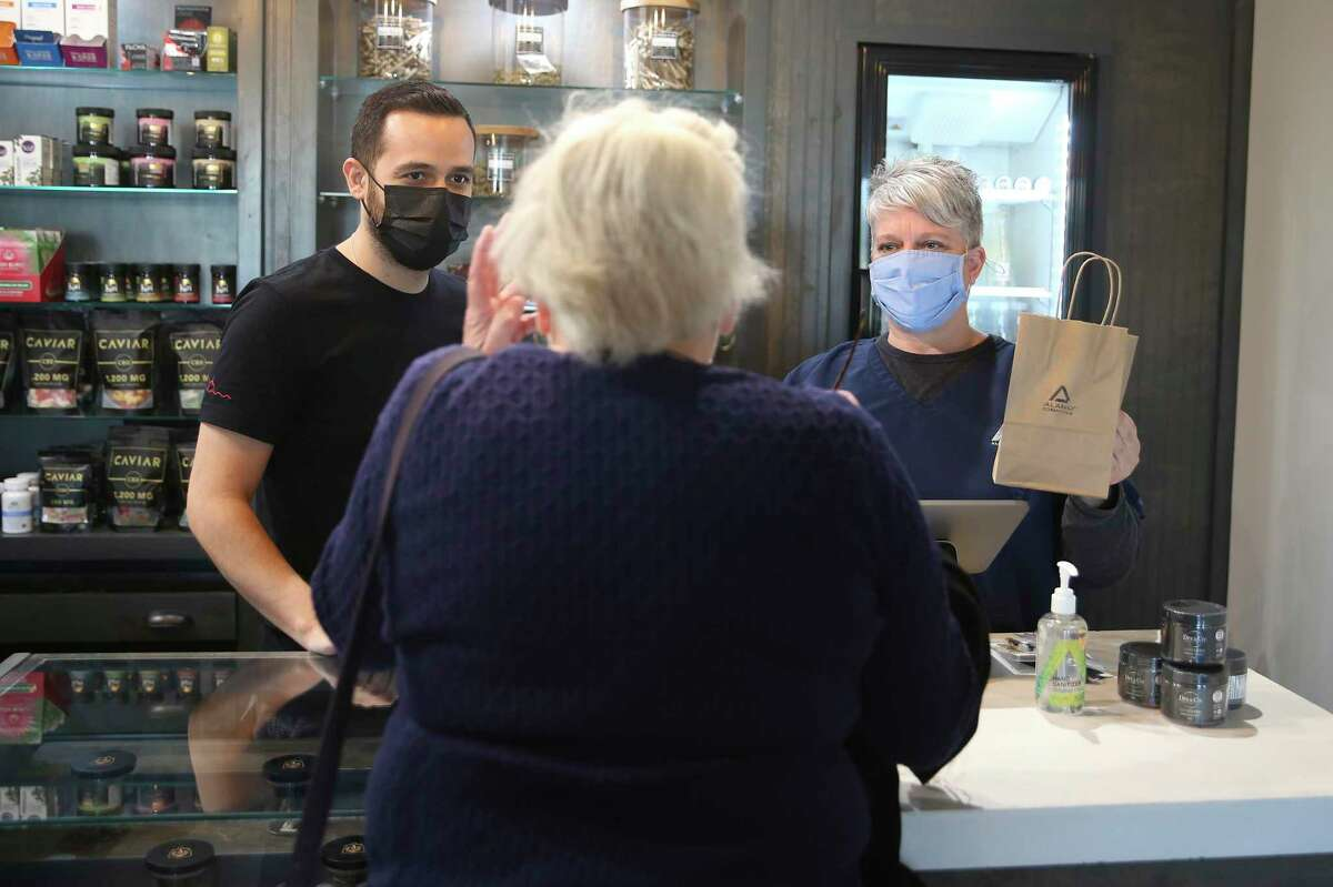 Owner David Burrow, 34, left, and Cheryl Merlock, 54, help a customer last week at one of the business's four locations.