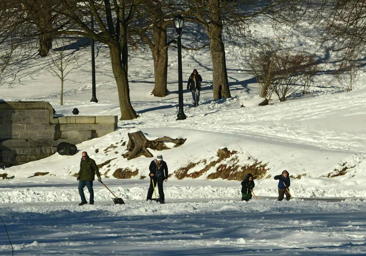 A family is seen shoveling snow to reveal the ice on the Washington Park Lake on Thursday, Feb. 4, 2021 in Albany, N.Y. (Lori Van Buren/Times Union)