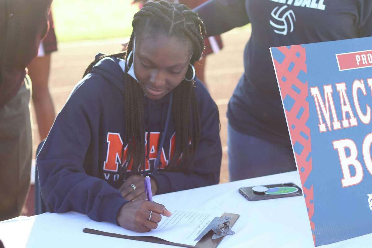 Northbrook's Torrance Williams celebrates signing her National Letter of Intent to play volleyball at Macalester College during a ceremony at the school on the morning of Feb. 3 for National Signing Day