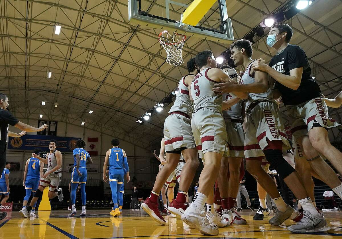 Stanford forward Oscar da Silva, second from right, celebrates with teammates after scoring in overtime for a victory in an NCAA college basketball game against UCLA in Santa Cruz on Jan. 23.