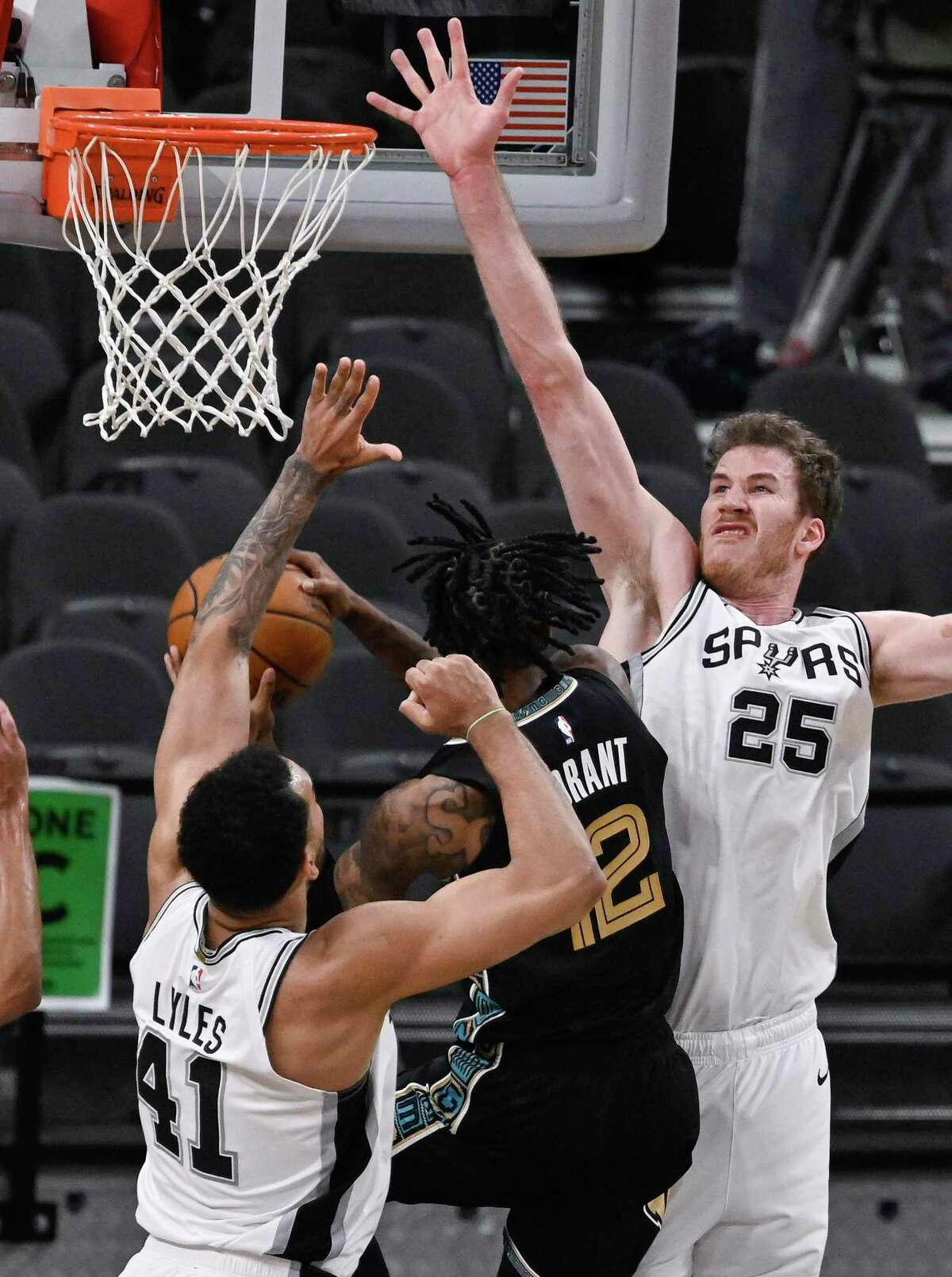 Memphis Grizzlies' Ja Morant, center, attempts to shoot against San Antonio Spurs' Jakob Poeltl (25) and Trey Lyles during the second half of an NBA basketball game, Saturday, Jan. 30, 2021, in San Antonio. (AP Photo/Darren Abate)