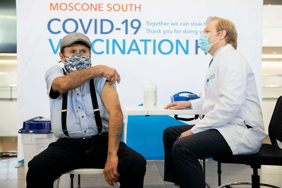 Raul Garnelo, 73, rolls up his sleeve to receive the very first dose of the Pfizer COVID-19 vaccine given ahead of the opening of a mass vaccination site at Moscone South in San Francisco, on February 4, 2021.
