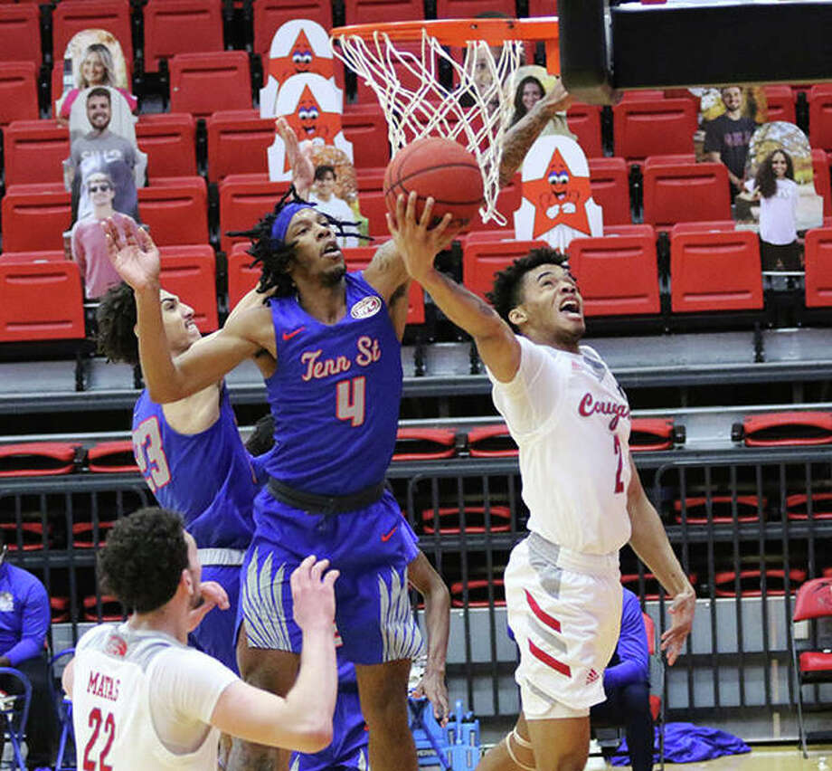 SIUE's Desmond Polk (right) gets off a reverse layup beyond the block attempt from Tennessee State's Shakem Johnson (4) on Thursday afternoon at First Community Arena in Edwardsville.