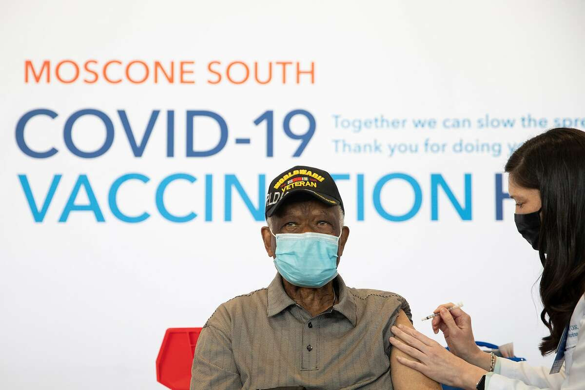 Ezekiel Logan, a 96-year-old World War II veteran, receives his first dose of the Pfizer COVID-19 vaccine this month ahead of the grand opening of a mass COVID-19 vaccination site at Moscone South in San Francisco, which is partnered with Kaiser Permanente.