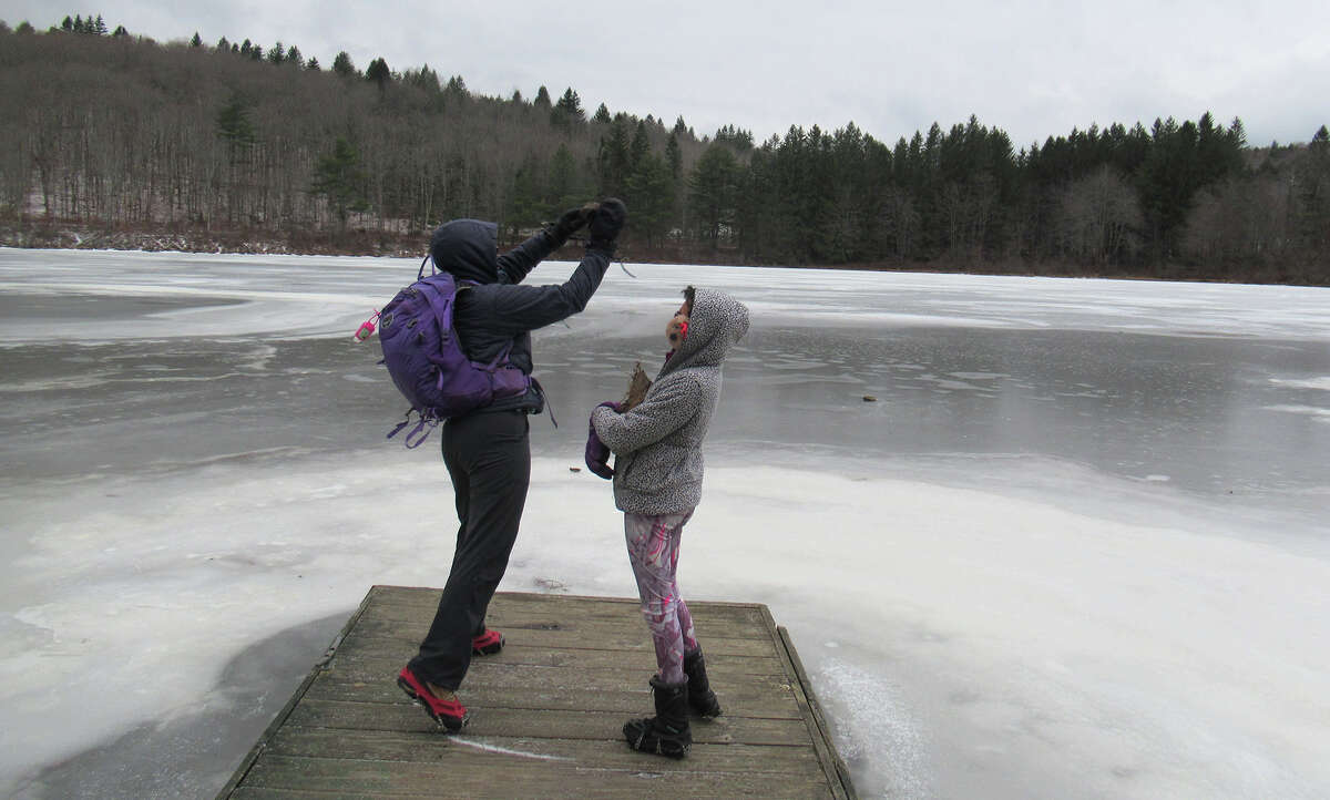 Gillian Scott tries to smash through the ice with a rock at White Birch Pond in the Partridge Run Wildlife Management Area.