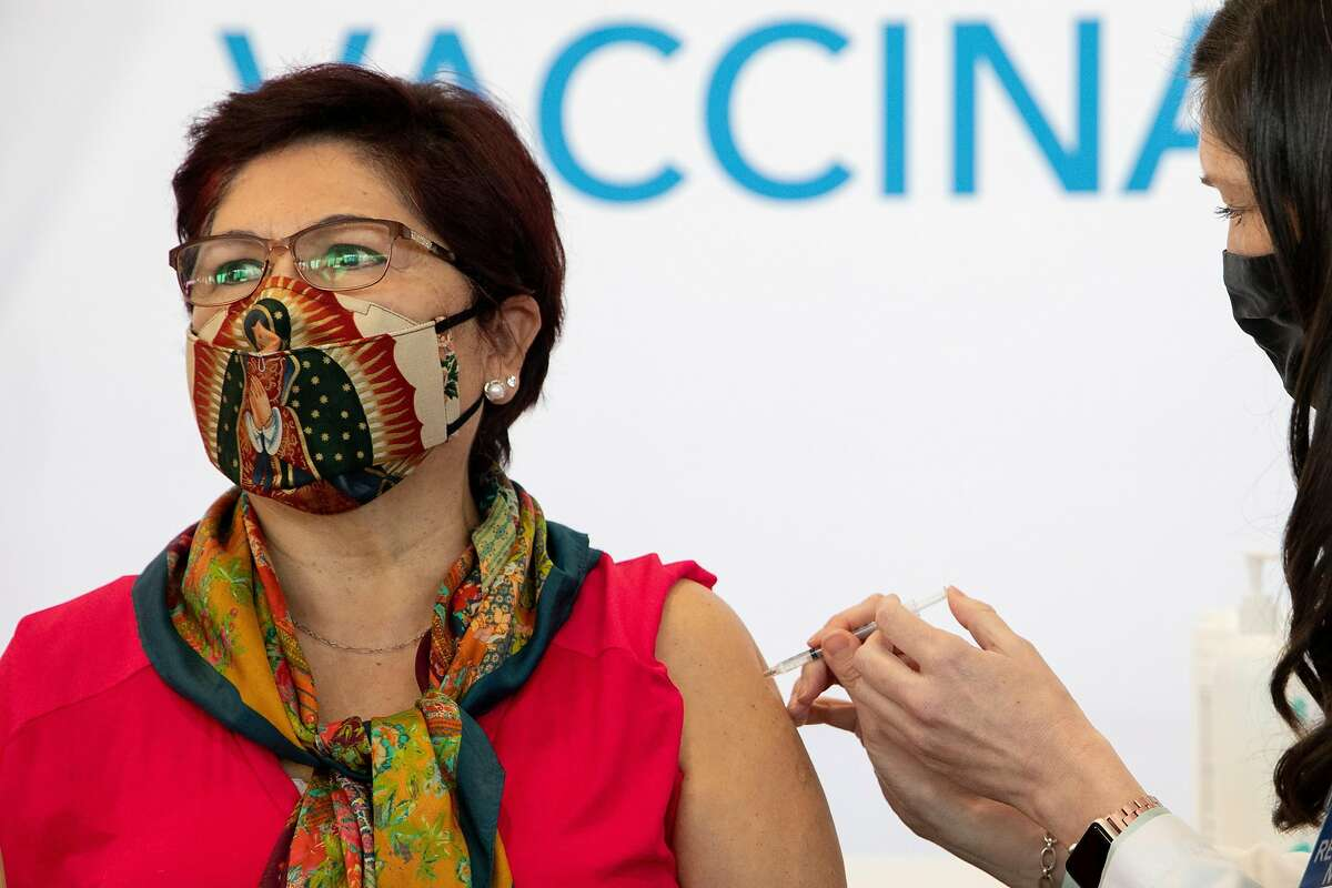 Irene Villa, 72, receives her first dose of the Pfizer COVID-19 vaccine ahead of the grand opening of a mass COVID-19 vaccination site at Moscone South in San Francisco.