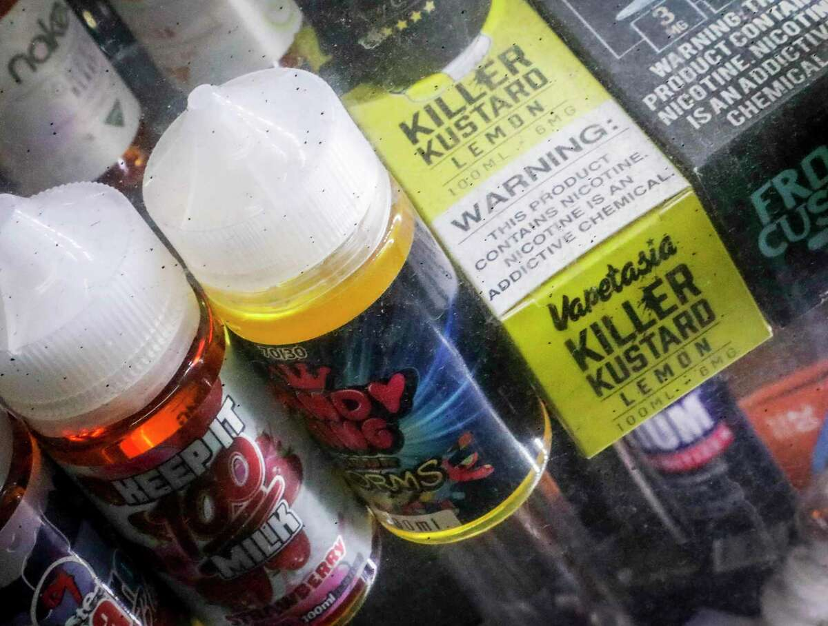 Flavored vaping solutions in a window display at a vape and smoke shop in New York.