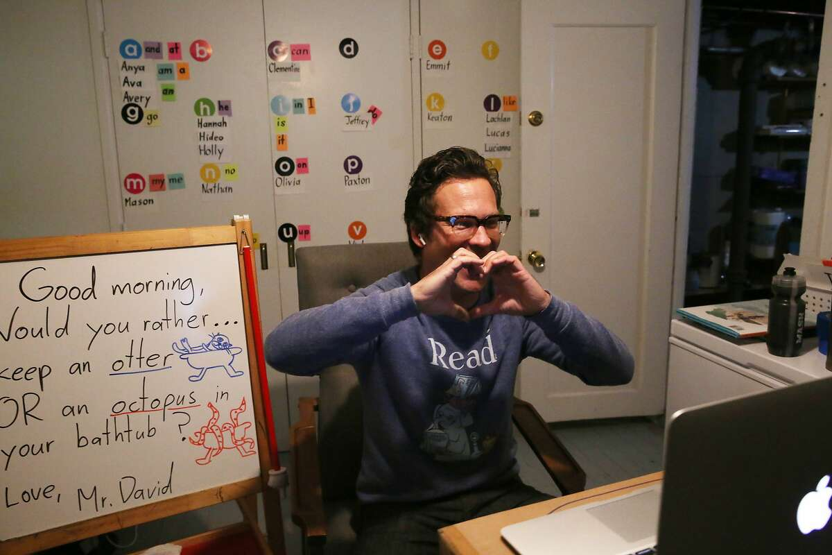 """David """"Mr. David"""" Moisl, uses his hands to make the shape of a heart as he says goodbye to his students before a break as he virtually teaches his West Portal Elementary kindergarten class from his home on Wednesday, February 3, 2021 in San Francisco, Calif."""