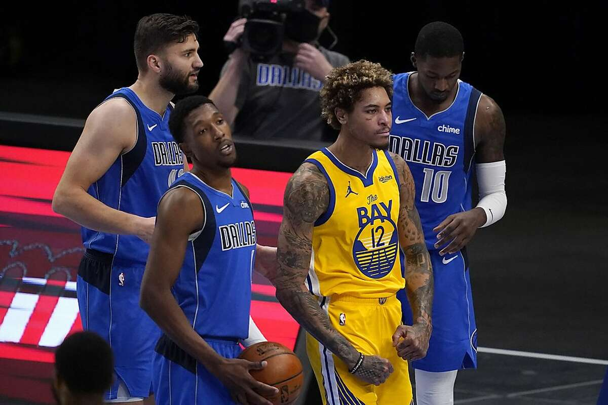 Golden State Warriors' Kelly Oubre Jr. (12) flexes after being fouled by Dallas Mavericks' Dorian Finney-Smith (10) on a shot attempt during the first half of an NBA basketball game in Dallas, Thursday, Feb. 4, 2021. The Mavericks' Josh Richardson, front, and Maxi Kleber, rear, stand nearby. (AP Photo/Tony Gutierrez)