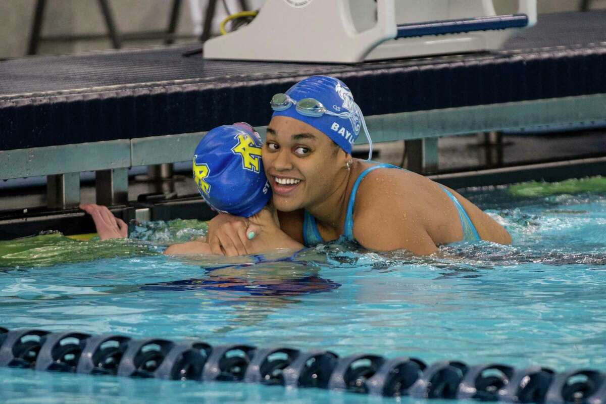 Madi Baylor of McCallum hugs Elizabeth Stromberger of Anderson after narrowly beating her in the 50 freestyle. Stromberger came back to beat Bayor in 100 freestyle event so both girls will compete in their respective race in the state competition next week.