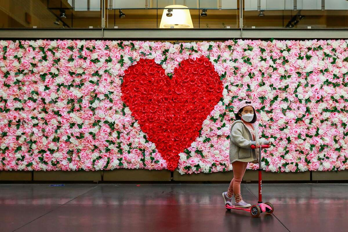 Olivia Kim, 5, (center) scoots past a floral Valentine's Day themed backdrop set up at the Ferry Building on Thursday, Feb. 4, 2021 in San Francisco, California.