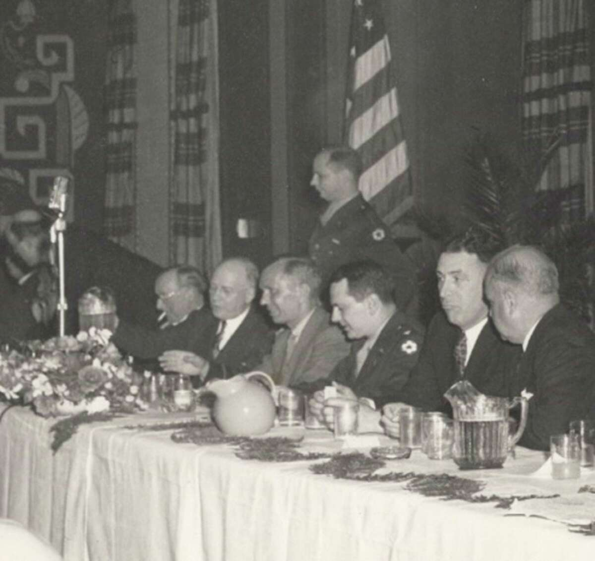 Captain Carl A. Gerstacker is standing behind R. Hoe company officials at a dinner elebrating the company's WWII work, April 16, 1945. Courtesy Rollin M. Gerstacker Foundation (Photo Provided)