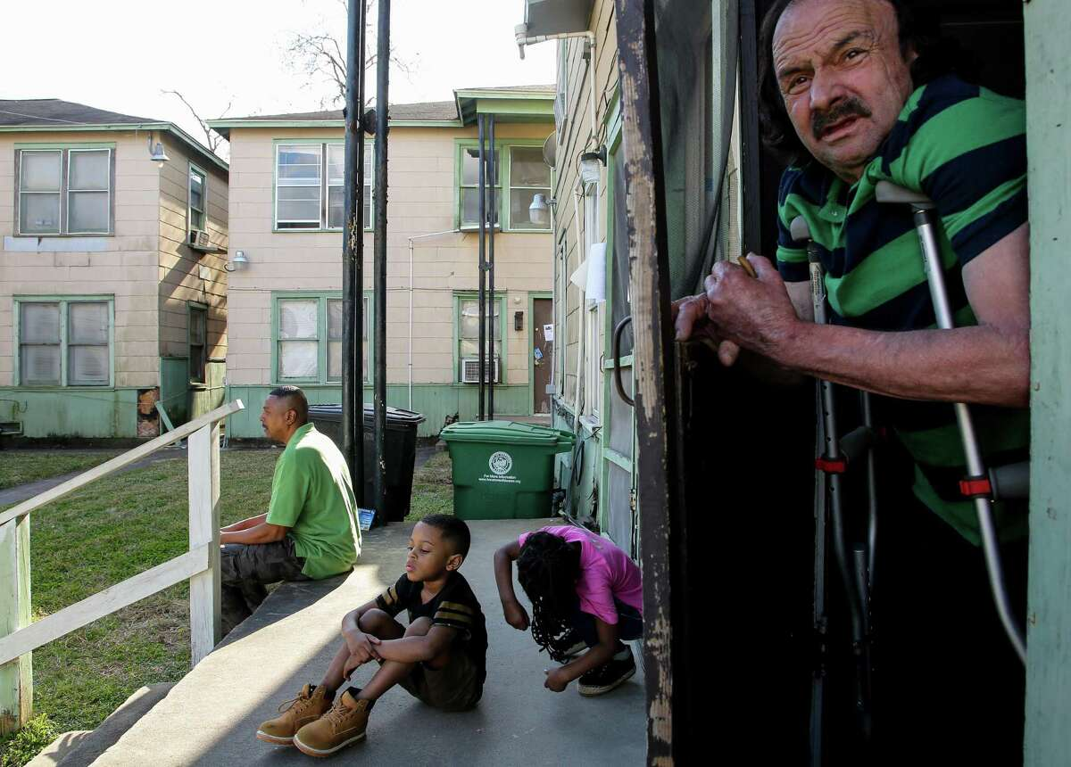 Damian and his sister Mya, center, play on the front steps of the building their father lives in, at 2210 Barbee St. on Wednesday, Feb. 3, 2021, in Houston. Residents have been given a deadline to move out of their apartments, following a change in ownership for the complex.