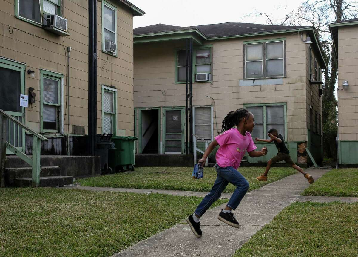 Mya and her brother Damian play on the courtyard at 2210 Barbee St. on Wednesday, Feb. 3, 2021, in Houston. Residents have been given a deadline to move out of their apartments after a new owner bought the complex.