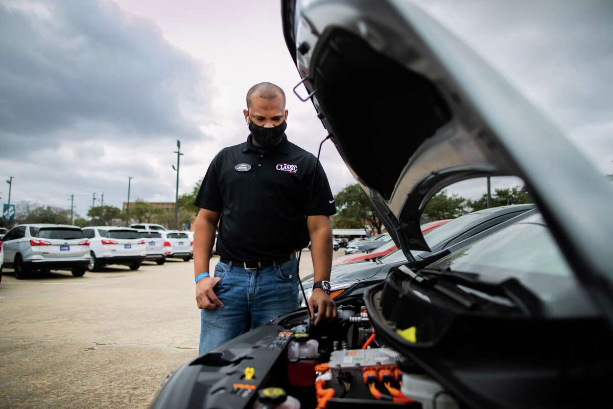Classic Chevrolet Sugar Land sales consultant Edward Jackson Davis takes a look under the hood of a Chevrolet Bolt EV, Thursday, Feb. 4, 2021, in Sugar Land. The Bolt EV is a front-motor, five-door all-electric car.
