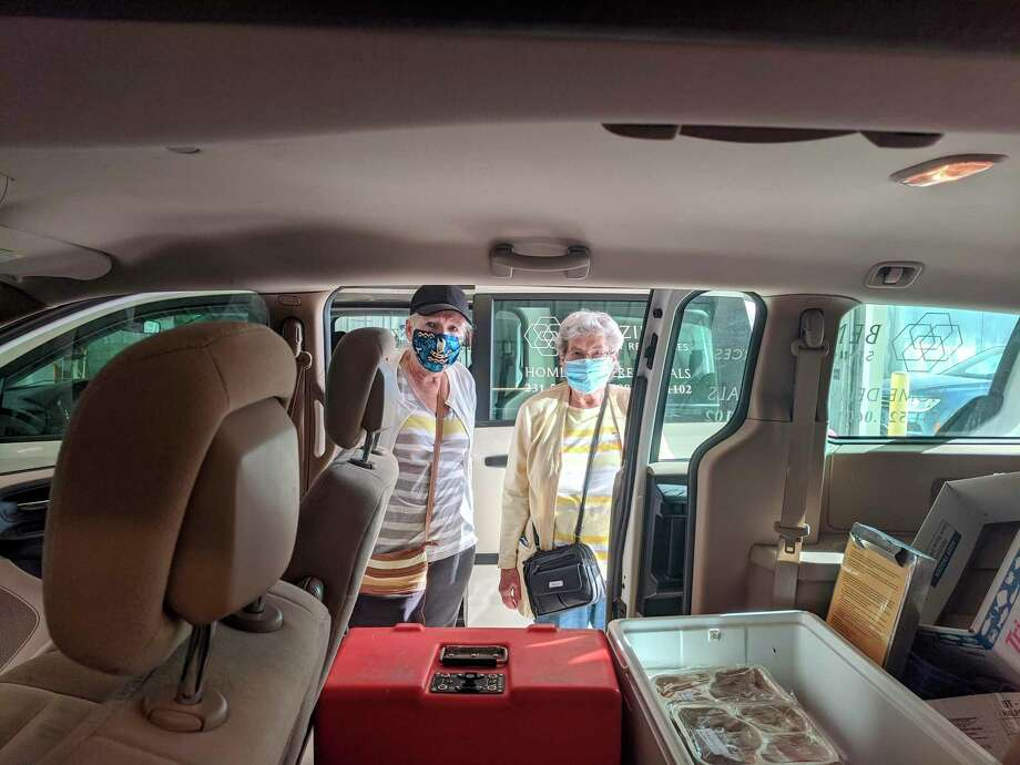 Volunteers with Benzie Senior Resources load hot and frozen meals into a van for transport to clients. (Courtesy Photo)