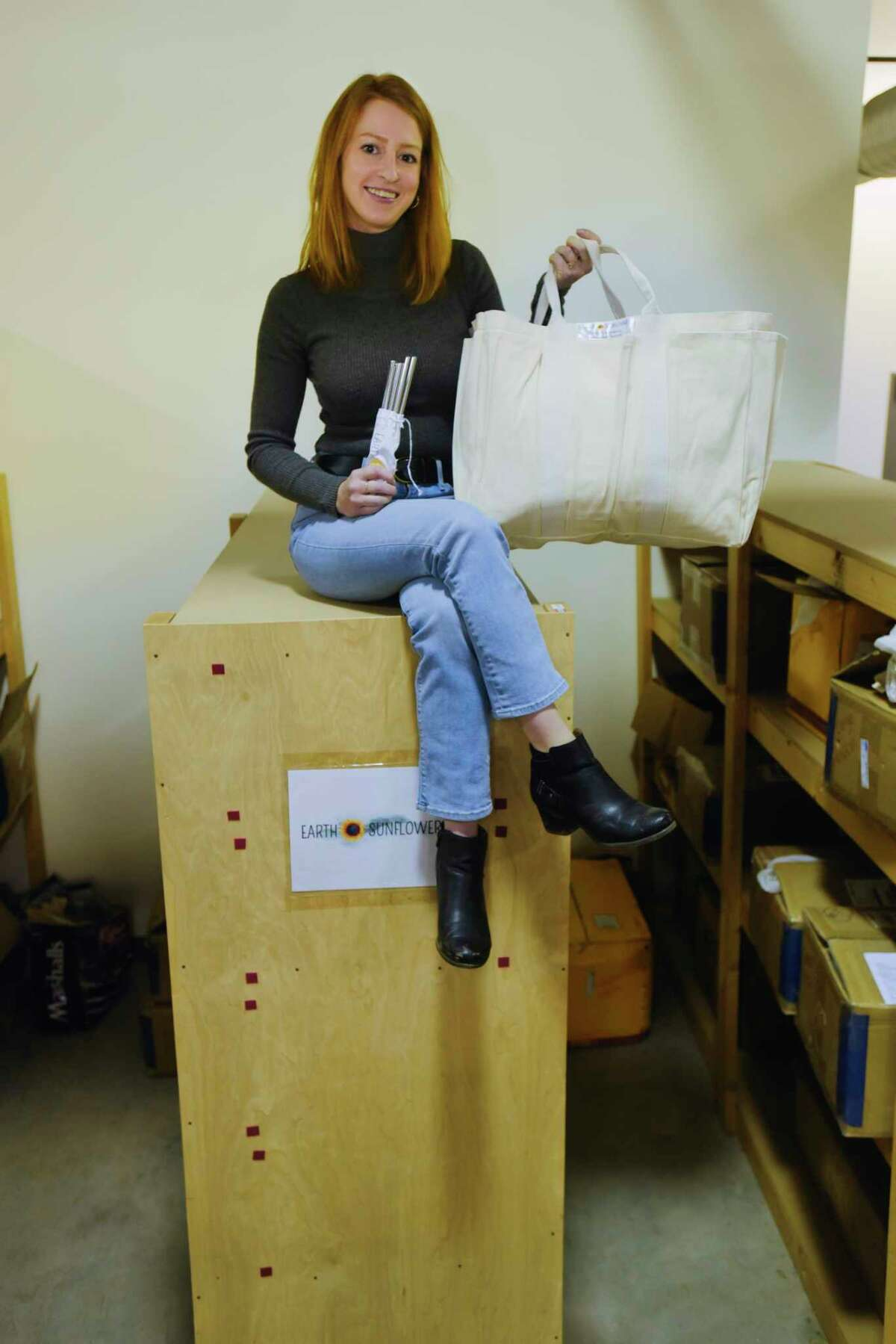 Jill Fecteau, owner of Earth Sunflower, sits on top of shelves holding boxes of the products she sells inside a warehouse where she rents space on Wednesday, Jan. 27, 2021, in Saratoga Springs, N.Y. Fecteau is holding stainless steel straws, which she started her business with, and a certified organic cotton extra large grocery bag with outside pockets, one of her bigger selling items currently. (Paul Buckowski/Times Union)