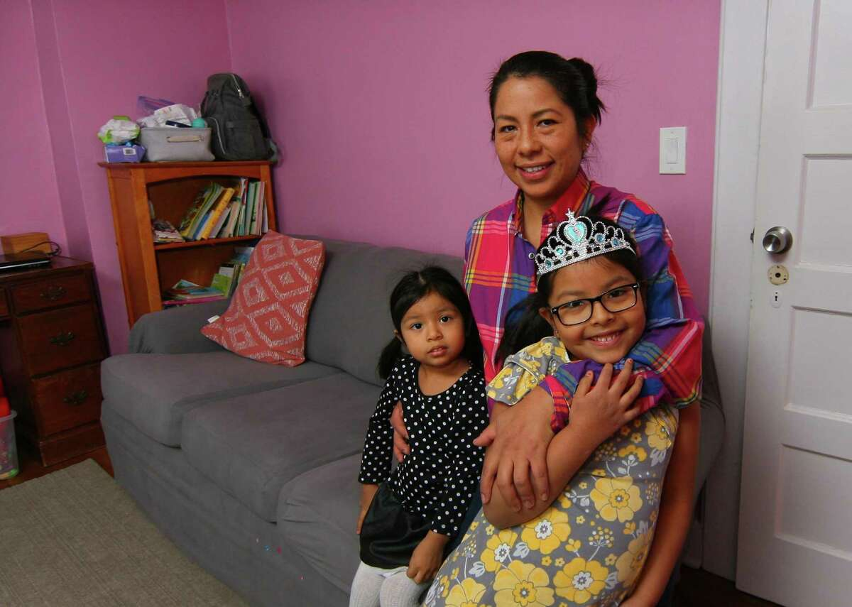 Flor Melgar poses with her children Annie Arrecis, 2, and Sofia Arrecis, 5, at their home in Port Chester, New York, on Saturday Jan. 30, 2021. Melgar receives help in educating her children through the Giving Fund and Family Centers.