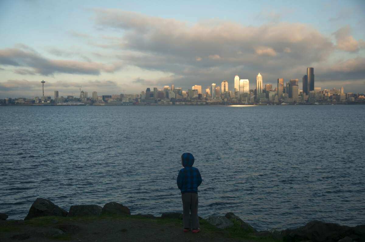 Silhouette of boy looking out at Seattle skyline from Alki Beach in West Seattle.