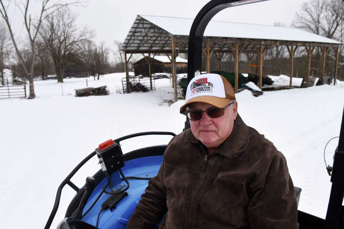 Louis Gnip sits on his tractor at the family farm off Brownell Road on Friday, Feb. 5, 2021, in Malta, N.Y. Gnip is working to preserve the family farm from development. (Will Waldron/Times Union)