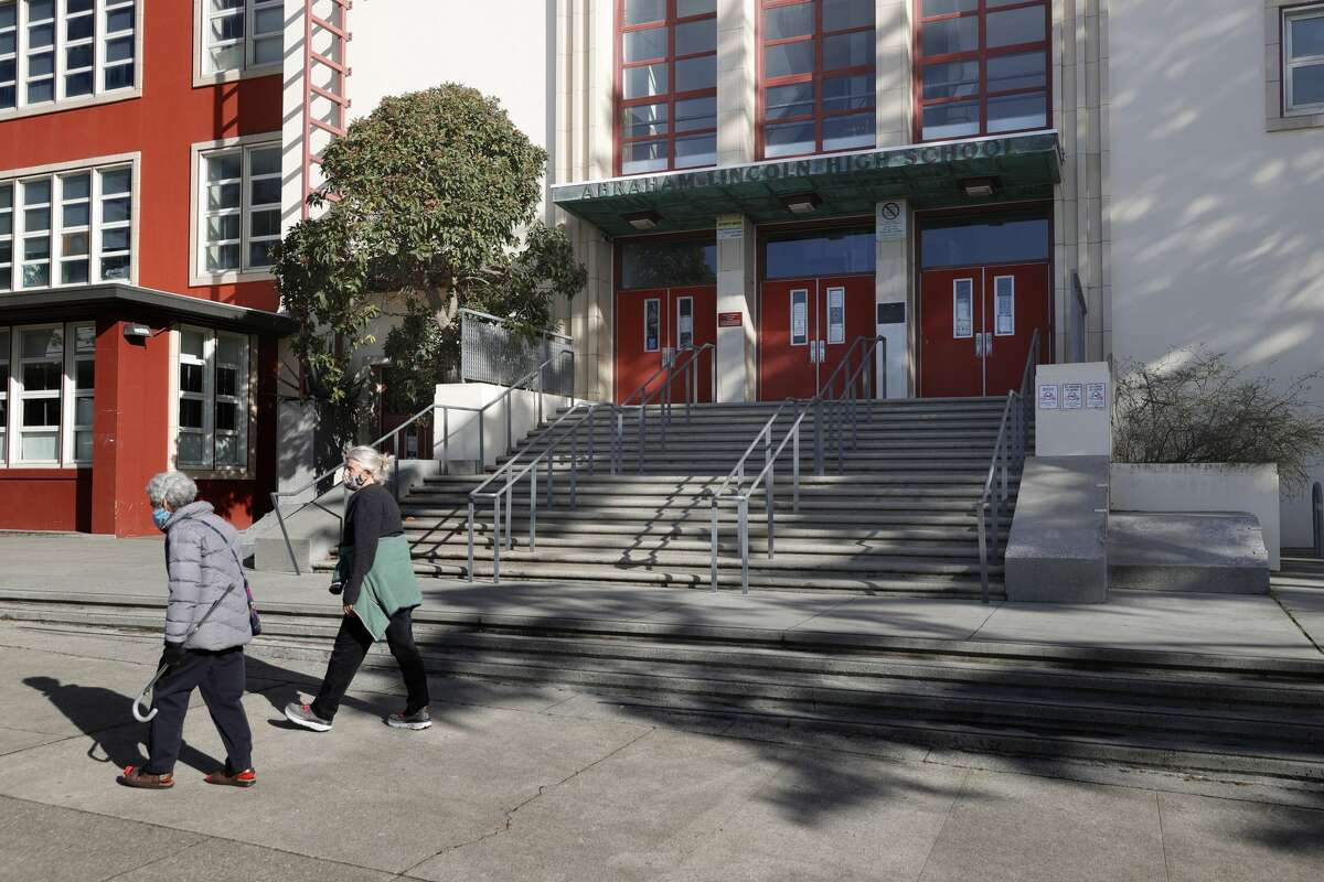 Pedestrians walk by the main entrance of Abraham Lincoln High School on Dec. 17, 2020, in San Francisco.