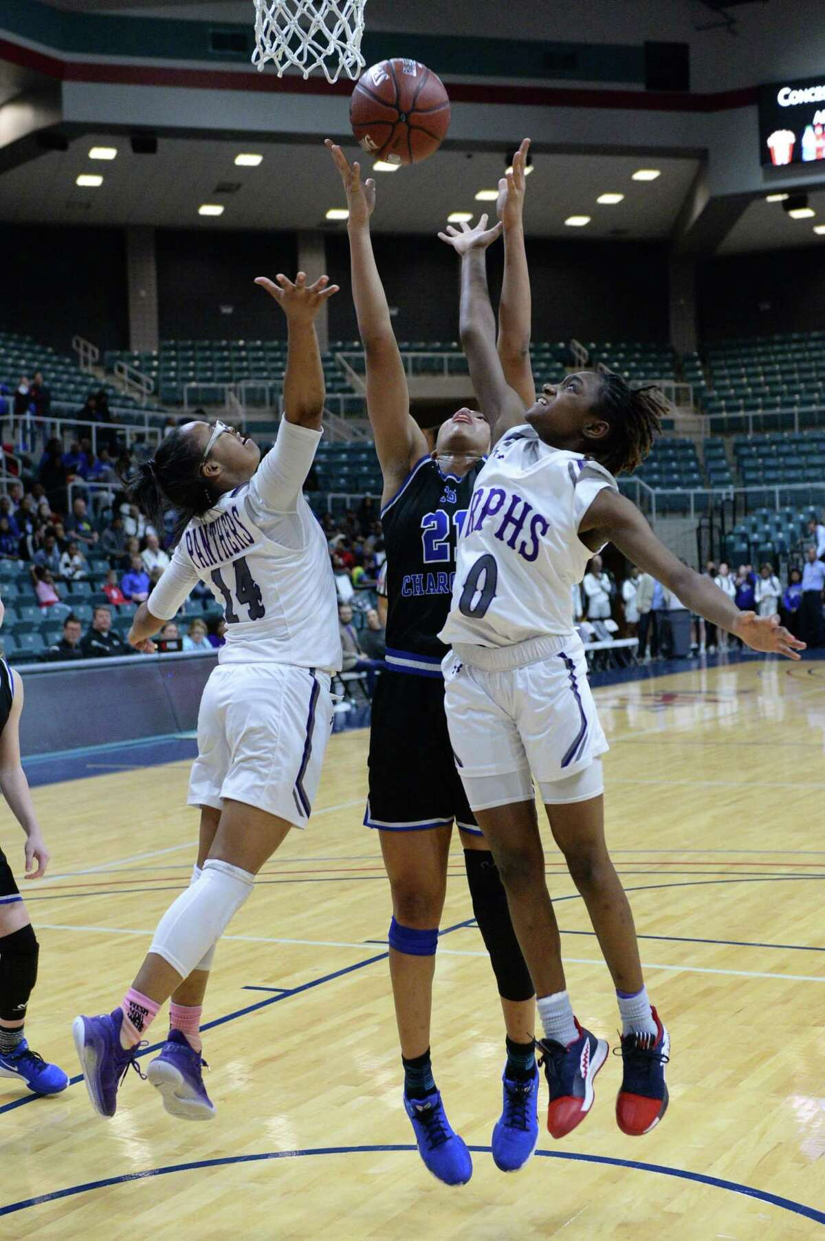 Aleighyah Fontenot (14) and Raven Adams (0) of Ridge Point compete with Niyah Johnson (21) of Clear Springs for a rebound during the fourth quarter of a Girls 6A Region III semifinal play-off game between the Ridge Point Panthers and the Clear Springs Chargers on Friday, February 28, 2020 at the Leonard Merrell Center, Katy, TX.
