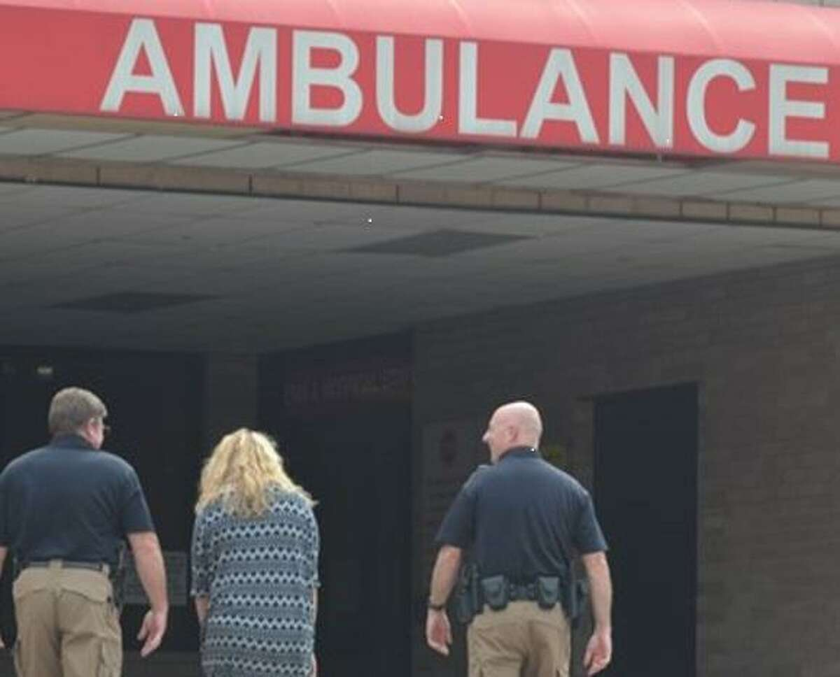 A person, center, following a mental health crisis is escorted into the HCA Houston Healthcare Conroe emergency wing by Montgomery County Precinct 1 Constable's Deputy Rick Fought, left, and Lt. Brian Luly, right, both of the county's crisis intervention team.