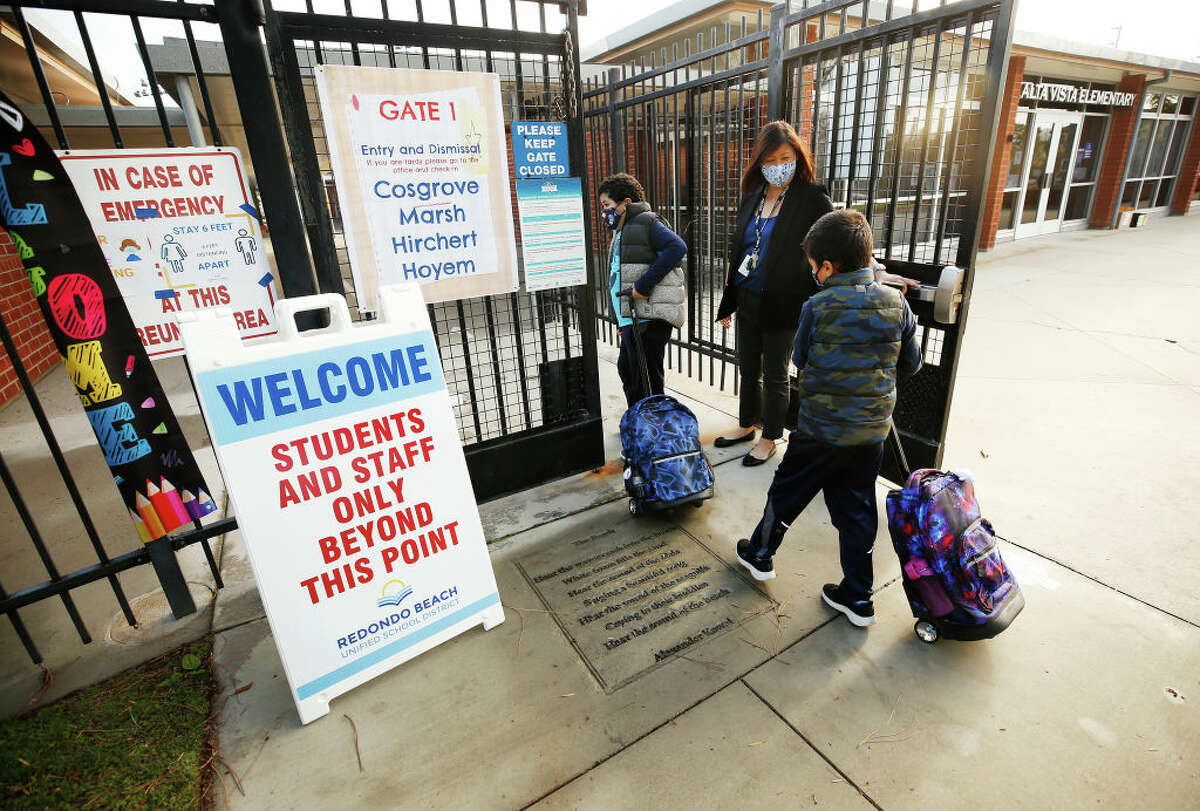 Alta Vista Elementary School Principal Karin Sato opens the door for first grade students Knoah Aracena, left and twin brother Kane Aracena after they are screened for the second day of classes as Redondo Beach Unified School district has welcomed back some of its K-2 students this week through a waiver. Alta Vista Elementary School on Tuesday, Feb. 2, 2021 in Redondo Beach, CA.