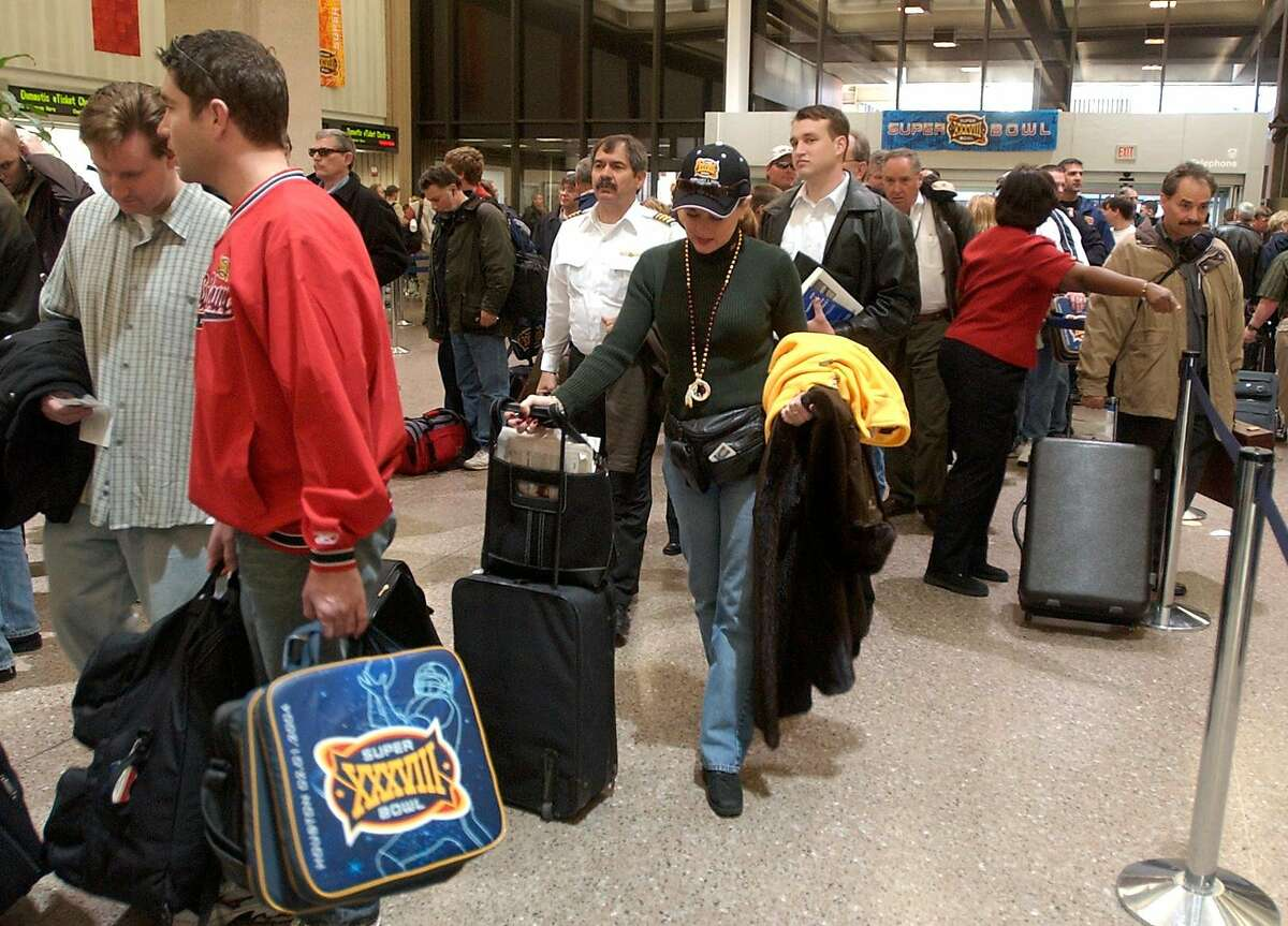 01/02/04--Steve Snyder, left, (red shirt) carries seat cushions through security lines at the airport and Karen Guise (center) wears her Suprebowl hat as they each prepare to leave Houston after attending the game. Snyder was returning home to San Diego, Calif. and Guise was continuing her vacation by going to Vale Colorado to Ski. (Note: they were not together) Passengers crowded Bush Intercontinental Airport as they return home from the Superbowl. Photo by Steve Campbell