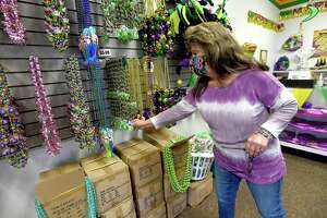 Jeanine Hebert turns on a lighted bead strand, which is among the newest items for sale at The Mardi Gras Store in Port Arthur, where business has been steady amid a largely cancelled Mardi Gras celebration season. Photo taken Thursday, February 2, 2021 Kim Brent/The Enterprise