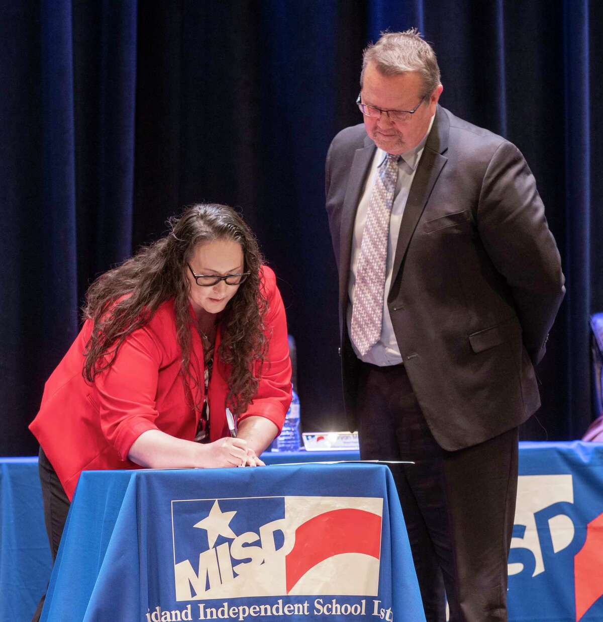 Angelica Ramseysigns her contract with board president Bryan Murry, following a unanimous vote in February after the MISD school board approved the hire of the then-superintendent candidate. Tim Fischer/Reporter-Telegram