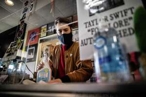 Steven Suarez, 33, disinfects his work space at Cactus Music, Wednesday, Feb. 3, 2021, in Houston. Suarez lost his job at Academy after a disagreement with a client at the sporting goods store who didn't want to wear a protective mask.