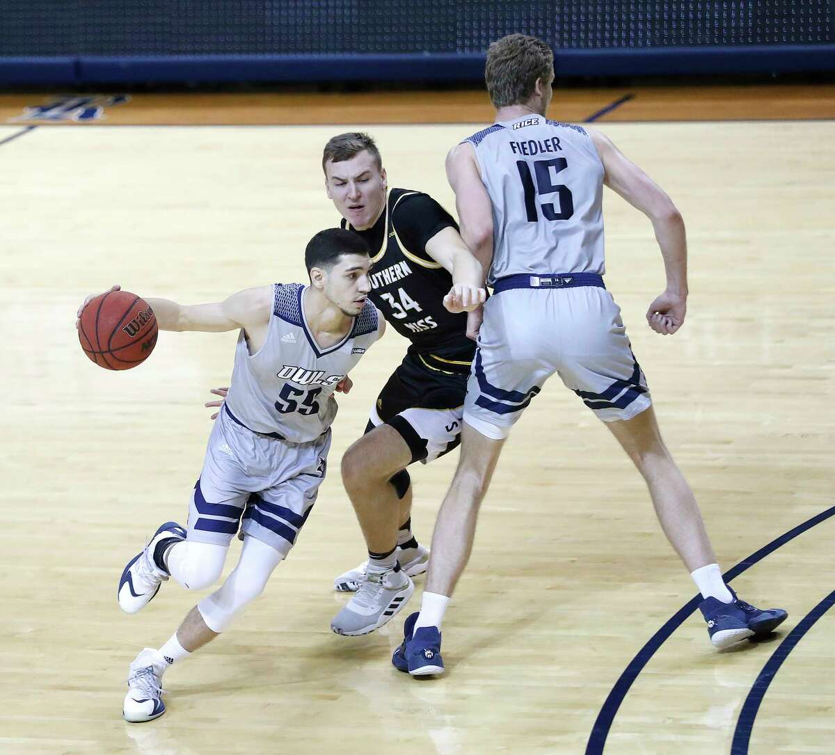 Rice Owls guard Cavit Ege Havsa (55) works past Southern Miss Golden Eagles forward Artur Konontsuk (34) as Owls forward Max Fiedler (15) set the pick during the first half of an NCAA men's basketball game at Tudor Field House in Houston, Friday, Feb. 5.
