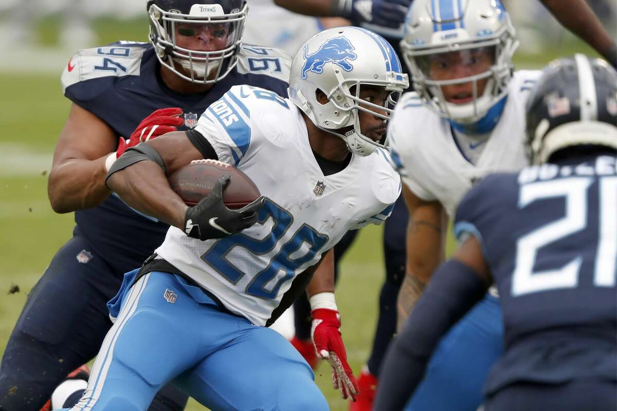 NASHVILLE, TENNESSEE - DECEMBER 20: Running back Adrian Peterson #28 of the Detroit Lions carries the football against the defense of the Tennessee Titans during the second quarter of the game at Nissan Stadium on December 20, 2020 in Nashville, Tennessee. (Photo by Wesley Hitt/Getty Images)