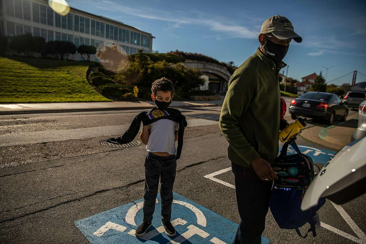 Reid Robinson, a first-grader and son of Kevin Robinson, puts on a sweater as his father picks him up from a community learning hub in San Francisco.