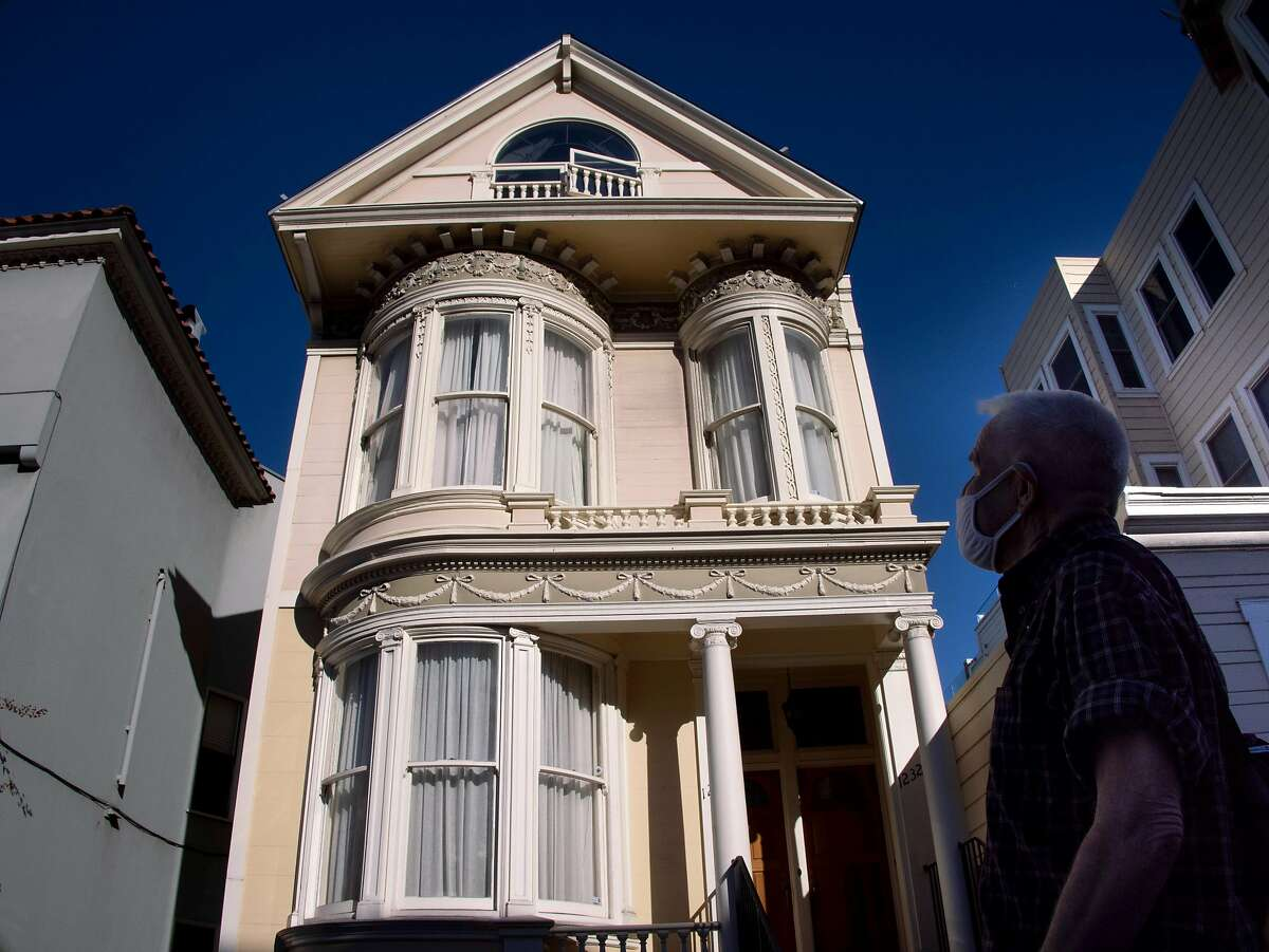 Denny Smith admires the curved glass in the windows of a victorian home on Friday, Feb. 5, 2021 in San Francisco, Calif.