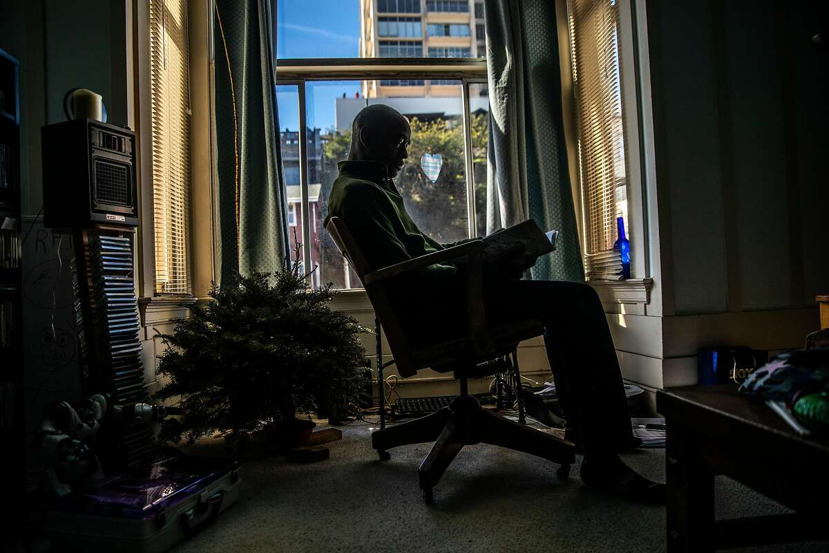 Kevin Robinson, a substitute teacher with San Francisco Unified School District, reads a book by a window in his North Beach home. Robinson, who has worked a total of seven days so far this school year, is hoping to go back to the classroom soon.
