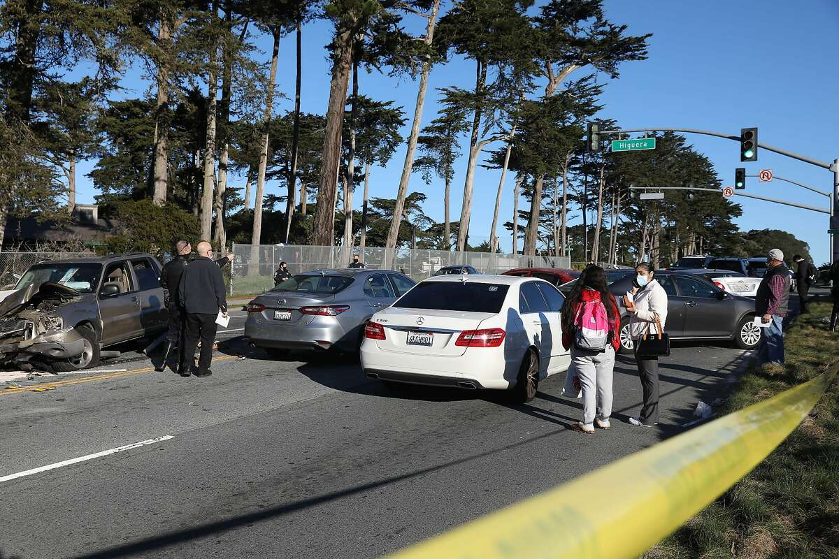 Emergency responders investigate at the scene of a multiple car collision as people stand next to cars on Lake Merced Boulevard on Thursday, February 4, 2021 in San Francisco, Calif.